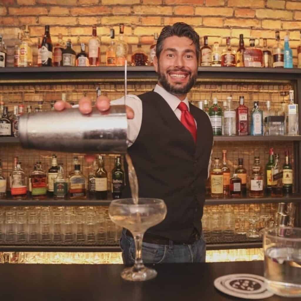 Experienced mixologist pouring a martini with a big smile