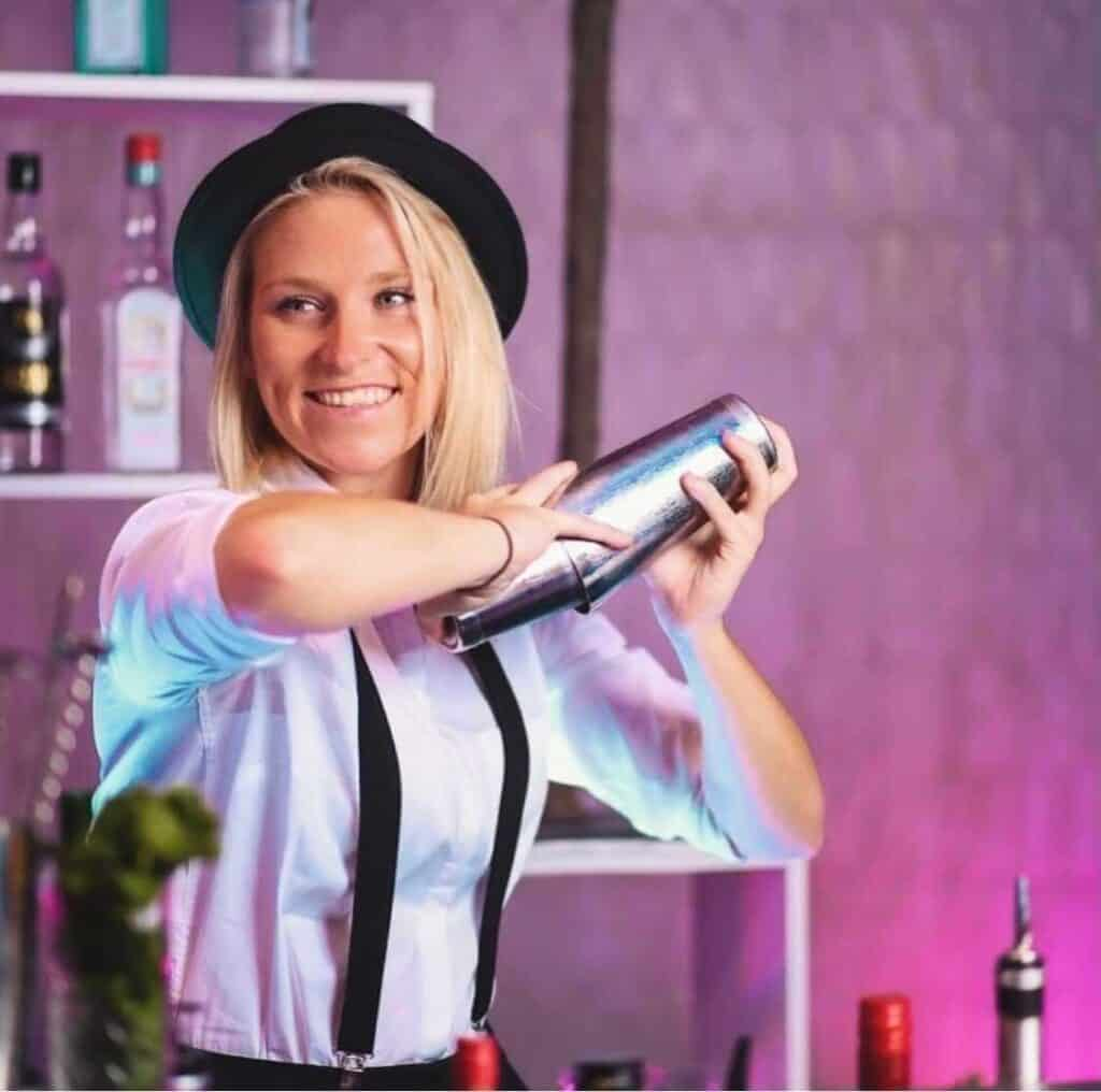 Cocktail bartender hire smiling and shaking a drink for a wedding