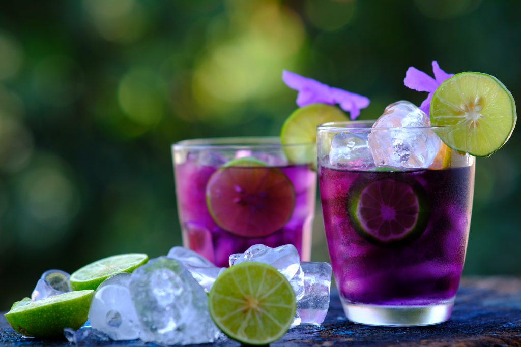 A stunning purple rain cocktail served with a lime